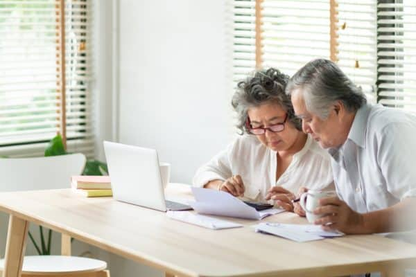 Stressed Asian Senior Couple using calculator and calculate family budget