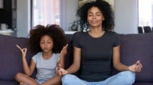 Mindful mom with cute funny kid daughter doing yoga exercise at home, calm mother and little girl sitting in lotus pose on couch together, mum teaching child to meditate