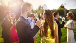 Wedding guests clinking glasses while the newlyweds drinking champagne in the background