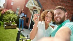 a young couple celebrate getting the keys to their new home by taking a selfie in the garden